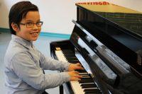 Odric (9 Jahre) am neuen Klavier